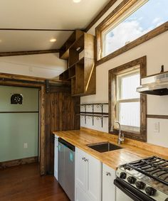 The kitchen includes a stainless steel three burner propane stove, butcher block counter, and under counter side-by-side refrigerator/freezer. Tiny House Swoon, Best Tiny House, Side By Side Refrigerator, Refrigerator Freezer, Best Camping Stove, Little Houses, Tiny Houses, New Stove, Clerestory Windows