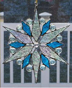 This stained glass starburst snow flake suncatcher wall hanging is finished in a Tiffany style copper foil technique and is approx. 9 H X 8 W