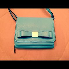 """NEW Merona Robin's Egg Blue Crossbody Bag NWOT Brand New Without Tags Merona Crossbody Bag in a great Spring Color-Robin's Egg Blue!  Has a VERY CUTE Bow on front of bag which makes it look VERY similar to a KS Bag.  Measures 6.5"""" X 5.5"""" X 1.5"""".  Has a built in phone pocket (holds an iPhone 6) on front of bag but hidden when flap of bag is closed by Magnetic Closure.  Inside has a zippered pocket plus 3 slots for Credit Card, License etc.  Never Used.  Perfect for Spring!! Any Questions…"""