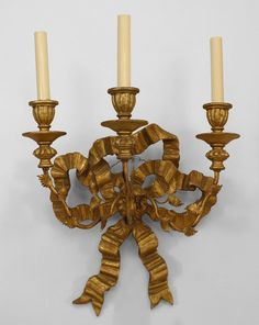 Part of a pair of French Louis XV style gilt (19/ 20th Cent) wood bow knot back wall sconces with 3 gilt metal arms.