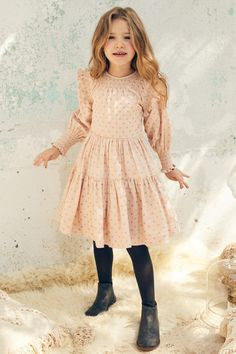 Nellystella's Celia Girls Dress is a sweet, tiered long sleeve girls dress which features smocked detailing around the collar and sleeves and ruffles at the shoulders. Zipper closure at the back. Shell: 95% cotton, 5% lurex; Lining: 100% cotton.