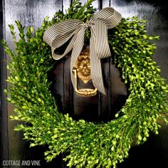 simple and classic boxwood wreath with black and white striped ribbon - Cottage and Vine
