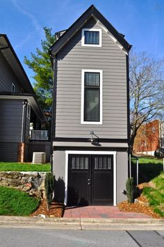 The Birdhouse, a tall and skinny 401 sq ft tiny house with the kitchen, living room and bedroom each occupying one of the three floors. | Tiny Homes