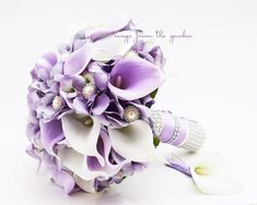 This real touch custom silk flower bridal bouquet of lavender silk hydrangea and white and lilac calla lilies sparkles with rhinestone and pearl accents.  I can create it for you as shown or customize it to fit your color scheme. We can work together to create a custom silk flower wedding package for your entire wedding party with your custom bridal bouquet, groom's boutonniere, bridesmaids' bouquets, mothers' corsages and more! Contact me today and we can get started on your cust...