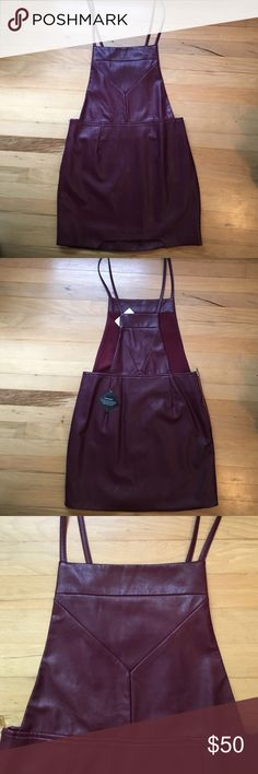 NastyGal Burgundy Leather-like Overall Dress NWT! Never worn NastyGal overall dress with burgundy leather-like fabric. Beautiful color, unique stitching details, and a little semi-circle cut out on the thigh, this item is super cute paired with a crop top underneath. NWT! Nasty Gal Dresses