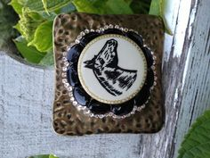 Vintage horse show ribbon button set into center of pounded brass buckle surrounded by black onyx stones and a row of Swarovski crystals