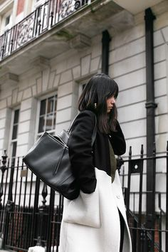 Nisi is wearing:  Céline Edge bag, Gucci Princetown slipper, Üterque two-tone coat,green sweater, skinny jeans - teetharejade.com
