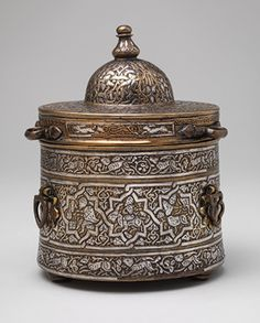"""Inkwell with Zodiac signs, Seljuq period (1040–1196), early 13th century, Probably Iran, Brass; cast, inlaid with silver, copper, and black compound, H.(14.9 cm),H. without lid(9.2 cm), Diam.(11.6 cm)  Harris Brisbane Dick Fund, 1959 (59.69.2a,b)  The inscriptions on the lid of this inkwell convey generic blessings for the owner, and are """"animated,"""" that is, parts of letters are transformed into animal or human figures. The base of the inkwell is decorated with signs of the Zodiac."""