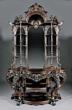 "American Rococo carved and laminated rosewood étagère. This mid-19th century beauty attributed to John and Joseph W. Meeks, NY and boasts a floral carved strapwork crest. Standing 104"" tall, the étagère has a segmented arched mirror back flanked by six shelves on turned supports. A curvaceous serpentine top with a reticulated apron adds to the piece's overall appeal as do its cabriole legs and scroll feet. #AntiqueFurniture"
