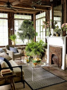 The sunroom's salvaged casement windows, vintage fireplace surround, and Plexi-Craft coffee table exemplify the owner of this Connecticut farmhouse's new-meets-old mix.
