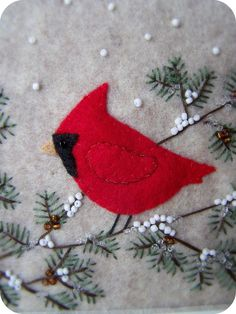 """Oatmeal felt background with our cardinal perched on pine branches.  Snow and pine cones created with seed beads.  Frame is 8""""x11"""" and art is 5""""x7""""."""