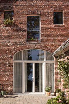 Ehemaliges Scheunentor mit großzügiger Verglasung : Puertas y ventanas rurales de Lecke Architekten