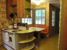 straight out of the 60s with bold veggie wallpaper, linoleum counter tops, rough cedar cabinets (with orange interior), and bright orange seating nook.  // found this kitchen on HGTV they hate it of course, I think it's awesome!!! retro vintage 1960s 1970s