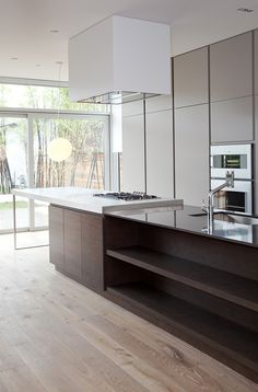 Minimalist Kitchen Design..... I love the zen feeling and clean lines in this kitchen.  The contrast of the dark cabinets against the white.... love the light wash wood floors (pinned by Danielle Lake Design, www.daniellelakedesign.com)