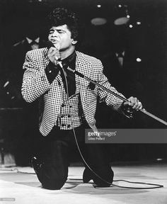 Photo of James BROWN; James Brown performing on stage, on knees