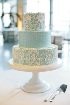 Stunning three tiered pale blue and white wedding cake with henna inspired paisley, floral and polka dot designs.