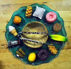 """a Chametz/Kasher L'Pesach sorting tray- find the Chametz and put it in the basket (you can also write """"Chametz"""" and """"Kasher L'Pesach"""" on 2 pieces of paper and have the kiddos sort the foods into the correct columns):"""