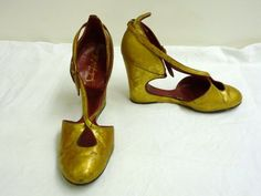 Pair of shoes   Saks Fifth Avenue   V&A Search the Collections: This is a trendy pair of shoes from the 1940s. They were retailed at Saks Fifth Avenue and made of leather in the USA. The wedge design seen here was made popular by Ferragamo, but this design has an unusual cut-out base. It is also painted gold and has a red leather trim and lining.