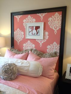 Frame out  with builder's molding, a large headboard.  Cover with complimenting fabric, and a frame within a frame for this look.