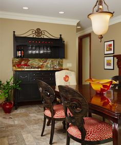 photo by Beth Singer  Dark wood bar accented by colored onyx, red leopard chairs are colored glass complete the space.