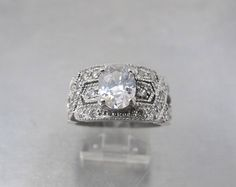 Stunning vintage signed CW for Charles Winston Sterling Silver Cubic Zirconia Solitaire Engagement Anniversary Ring with a gorgeous oval shaped beautifully faceted prong set Cubic Zirconia CZ stone in the center surrounded by brilliant pave set czs on a wide band with zig zag ornate design. A fabulous statement piece that will get noticed every time!  In great condition with all stones present brilliant and secure. Inside of ring has dulled a bit. This does not affect the look or…