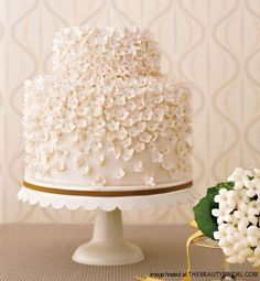 """Lovin Sullivan Stylish Wedding Cakes    Stephanotis sugar flowers """"look like a lush field of blossoms when repeated all over a wedding cake. For this creation, made of two equal-size tiers topped by a smaller one, Sullivan used a base of white fondant. She attached nearly 600 hand-made sugar-paste flowers using royal icing."""" In Style Weddings"""