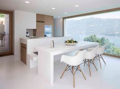 Wespi De Meuron Romeo Architects designed a minimalist house in Brissago, Switzerland, featuring all-white, meditteranean terraces wi. Kitchen Island For Dining, Open Kitchen, Rendered Houses, Eames, Beautiful Kitchens, Minimalist Home, Kitchen Furniture, Architect Design, Home And Living
