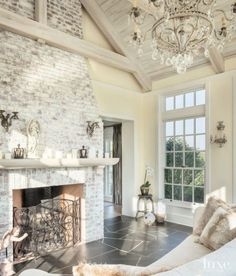 A crystal chandelier brings a touch of elegance to the solarium, which was designed as a retreat for homeowner Angela Kroeger. The fireplace is part of the same whitewashed brick massing used in the kitchen, and the fireplace screen features more of the o Modern Rustic, Modern Farmhouse, Rustic French Country, Painted Brick Fireplaces, Fireplace Brick, Fireplace Ideas, Brick Wall, White Fireplace, Fireplace Whitewash