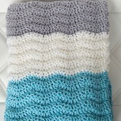 This free pattern creates a gorgeous, wavy, and colourful baby blanket.