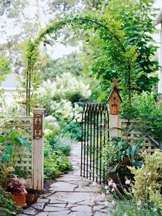 Whimsical Raindrop Cottage, love the arch, birdhouse, walkway, and mystery beyond the gate.