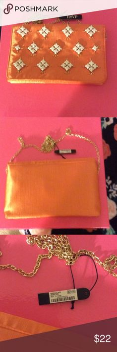 """RSVP Orange Satin Look Clutch with White Beads BWT RSVP orange silk look clutch bag with 23"""" gold tone chain.  Magnetic closure and one zippered compartment.  White square beads adorn the front of the bag surrounded by gold tone beads.  Extra beads are in the zippered compartment.  A lovely bag for that special affair.  Measures 9"""" x 6"""" x 1"""". RSVP Bags Clutches & Wristlets"""