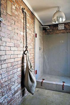 W tym wnętrzu pojawiają się wyłącznie materiały rodem z architektury przemysłowej: cegła, beton, metal i szkło / Industrial design bathroom.