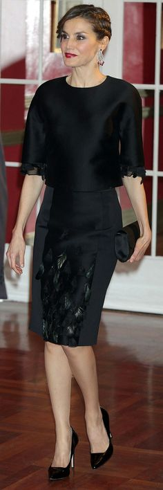 Queen Letizia - Carolina Herrera dress featuring a beautiful feather and bead applique on the sleeves and pencil skirt. She wore a piece from the designer's Pre-Fall 2015 collection featuring a beautiful feather and bead applique on the sleeves and pencil skirt.Letizia kept her accessories simple but made a statement with a new pair of dazzling diamond and ruby chandelier earrings, which she complemented with cherry red lipstick.