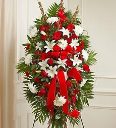 Sympathy Standing Spray in Christmas Colors. Let the traditional colors of the Christmas season become a lasting symbol of your sympathy and support with this graceful, hand-crafted Standing Spray. Beautifully designed using the season's freshest blooms. Elegant arrangement of red roses, carnations, hypericum and gladiolas, gathered with white lilies and cremones Designed by hand on a base of assorted Christmas greens and accented with pinecones, holly and red velvet ribbon An appropriate…