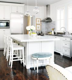 A lovely white kitchen.  Love the pop of color in the pale turquoise on the stool.