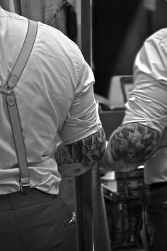 Rolled up sleeves, tattoo's, and braces.