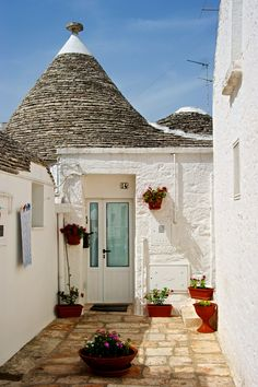 Trullo ( cone-shaped roof on stone hut house ) in Alberobello, Puglia - Italy - photo by Pascal Pro