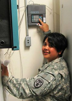 Sgt. Ninamarie N. Cruz, Administrative Officer of the Day (AOD), uses the Health Center's Sensaphone to gauge temperature levels of all refrigerators and freezers storing Temperature Sensitive Medical Products. At 3 a.m., Cruz makes her final check before annotating the temperature into the AOD logbook. (Photo courtesy of McDonald Army Health Center, Fort Eustis, Va.)