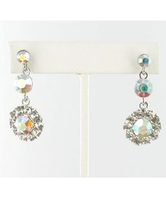 Exclusive formal pageant drop earrings X542. One of the most popular jewelry options, when it comes to a pageant competition, is earrings. These pendants are made of AB stones that come in a Silver or Gold Base, while crystal ornaments sit in the middle of the circular drop. Matching crystals embellish the post earring as well as the delicate accent that welcomes the dangly drop. Available in Gold AB, Gold/Clear, Gold/Topaz, Silver AB, Silver/Black, Silver/Blue, Silver/Clear, Silver/Emerald…