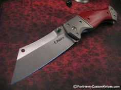 Randy Doucette's Jekel. With a unique Wharncliff / Cleaver combination blade this is a wonderfully unique large knife that can take care of business. The blade opens smooth as butter with either of the Dual Thumb Studs. This knife will fit your hand like a glove. The handles are beautiful Red G-10 that are precision fitted to the thick Titanum Frame. The bolsters are thick Matte Finished Titanium that have been contoured for a super feel when the knife is held.