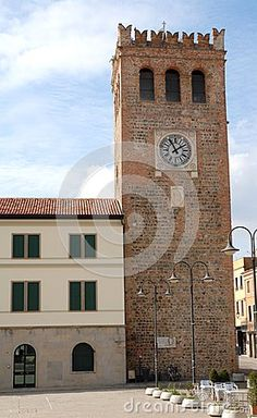Photo made in Monselice ancient medieval village that is located in the park of the hills Hills in the province of Padua in Veneto (Italy). In the image taken by the square of the ancient medieval tower, you see: a portion of the square with the streetlights in a row, the tower itself with a big clock, the next building with the facade in two colors an arched glass window and four windows closed.