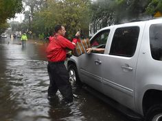 A firefighter helps a local resident on a flooded street