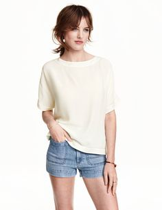 Check this out! Short, wide-cut blouse in woven crêped fabric. Slightly wider neckline, short cap sleeves, and rounded hem with slits at sides. - Visit hm.com to see more.