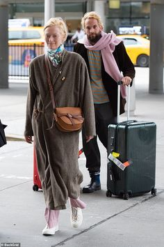 Tilda touches down at JFK Airport with Sandro Kopp, 41 - Keeping it low-key: The Hollywood actress, remained coy as she walked ahead of her par… - Tilda Swinton, Fashion Essentials, Jfk, Low Key, Angelina Jolie, Silk Scarves, Sandro, Hollywood Actresses, Older Women