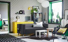 Szürke kanapé egy fekete zöld és sárga nappali közepén.IKEA