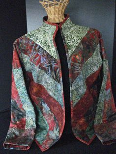 This lovely quilted jacket is made up of batik fabrics inside and out. It is in beautiful shades of red, rust, green and blue. The jacket has flannel