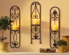 """Iron Candle Sconce Wall Trio   Light up your home with the romantic glow of candlelight by hanging this complementary trio of sconces on your wall. Each displays its own distinctive flourishes of fancy ironwork, and holds up to a 4 1/2""""Dia. pillar candle. Each measures 5 1/2""""W x 24""""H. Two hooks on back of each sconce for hanging."""