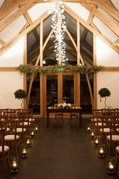 Mythe Barn ceremony with hurricane vases www.passionforflowers.net
