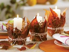 Candle holders with fall leaves.