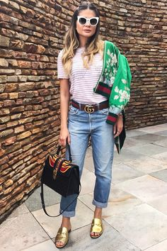 Street look de Thassia Naves com calça dobrada ao invés de levá-la para a costureira: economize e ainda fique muito mais cool! Blusa listrada com bomber jacket florida e mule dourado